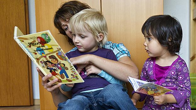 Muter liest mit zwei Kindern Bücher.