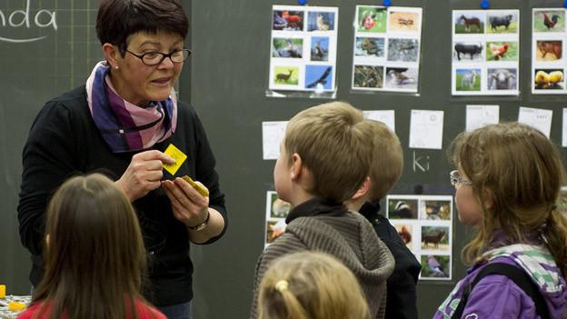 Schulkinder mit Lehrperson in Klassenzimmer