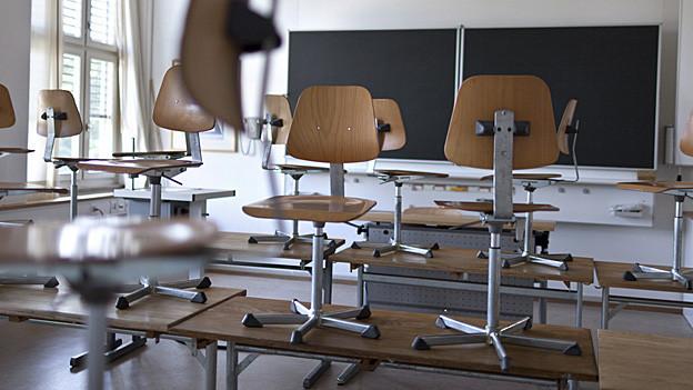 Stühle stehen im Klassenzimmer auf den Pulten