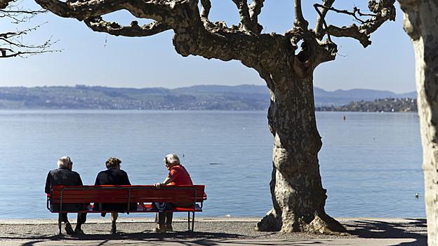 Drei Senioren sitzen auf einer Bank am See