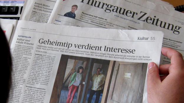 Mann hält aufgeschlagenen Zeitung in den Händen