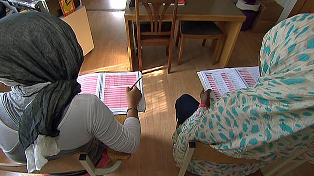 Zwei Mädchen tragen Kopftücher in der Schule.