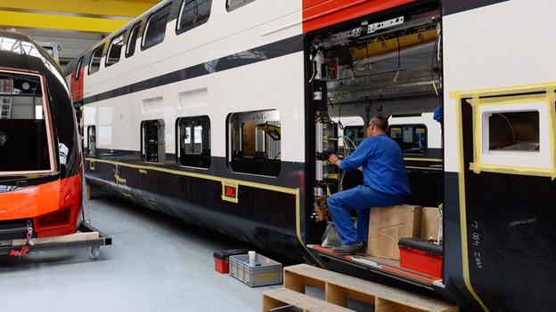 Fabrikhalle, ein Mann montiert einen Schalter an einen Zug.