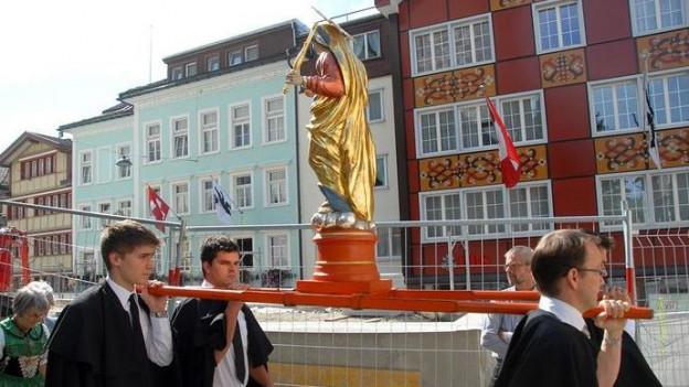 Männer tragen eine Statue von Maria