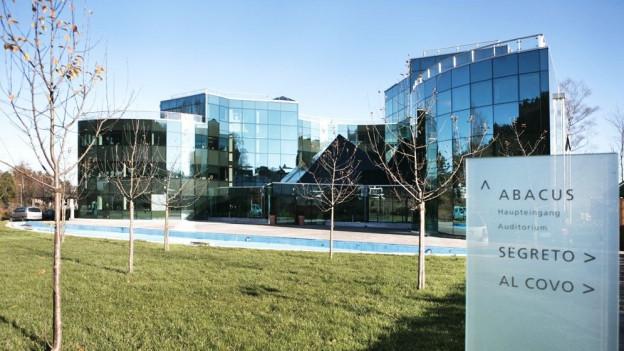 Firmengebäude mit Tafel und Aufschrift Abacus im Vordergrund