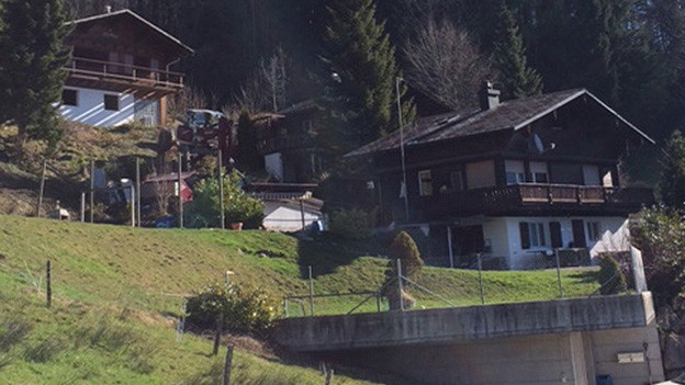 Zwei Holzhäuser am Hang.
