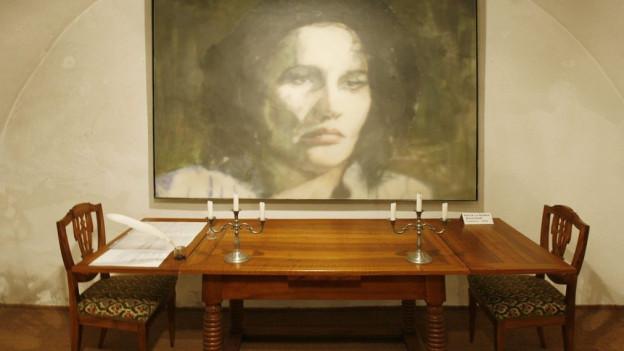 Ein Richtertisch und ein Porträt von Anna Göldi im ehemaligen Anna Göldi Museum in Mollis.