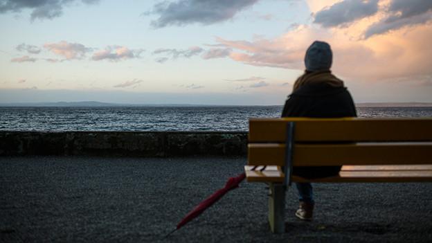 Frau blickt bei aufziehendem Sturm über den See.