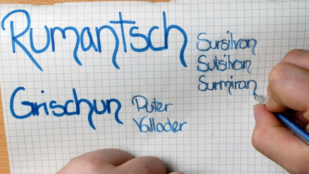 Eine Primarschuelerin notiert die verschiedenen Idiome neben der romanischen Schriftsprache Rumantsch Grischun.