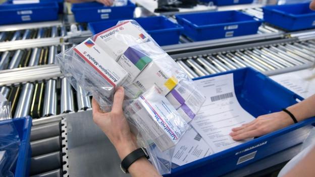 Eine Mitarbeiterin der Versandapotheke Zur Rose kontrolliert im Logistikzentrum in Frauenfeld anhand einer Liste eine Bestellung.