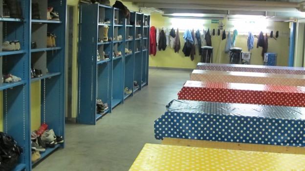 Regale mit Schuhen und Tische mit bunten Tischtüchern.