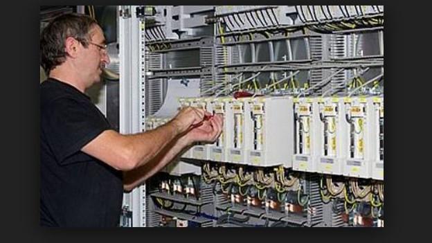 Mann arbeitet an einem Schaltkasten von Benninger