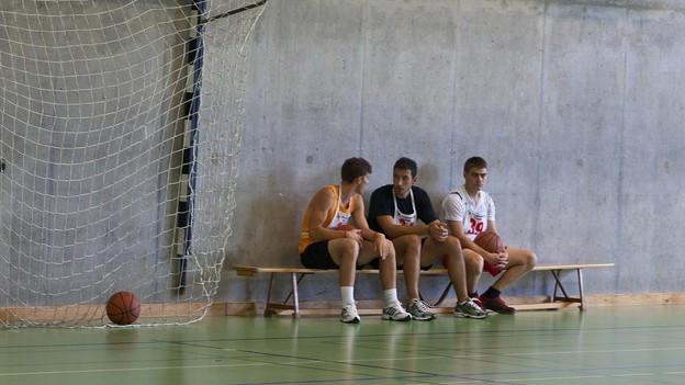 Drei Schüler sitzen in einer Turnhalle.