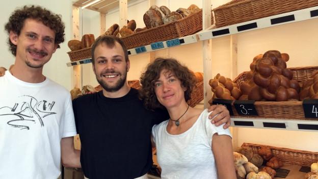 Drei Personen vor einem Verkaufsregal mit Brot.