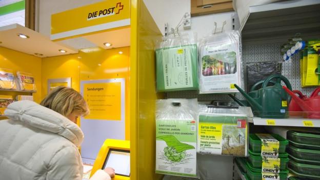 Frau am Schalter einer Postagentur.