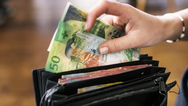 Frau nimmt Geld aus Portmonee.