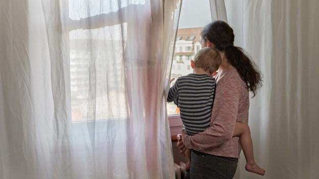 Mutter schaut mit Kindern aus dem Fenster