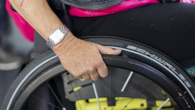 Frauenhand an Rollstuhlrad.