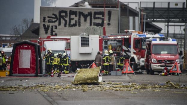 Trümmer liegen auf der Strasse vor Fahrzeugen der Feuerwehr nach einer Explosion bei der Chemiefirma Rohner in Pratteln.