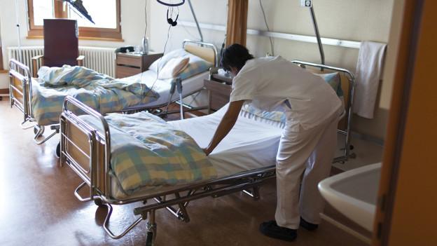 Spitalangestellte richtet Bett.