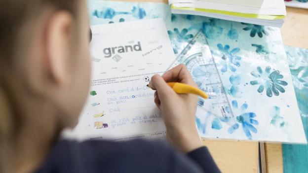 Schülerin beugt sich über Französischbuch