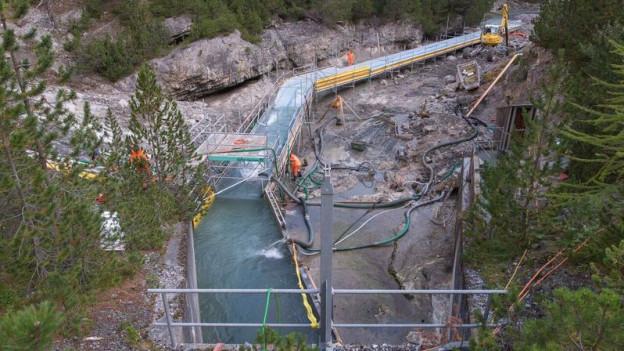 Mit grossem Aufwand wird der Spöl gesäubert. Teilweise muss das Flussbett ausgebaggert werden.