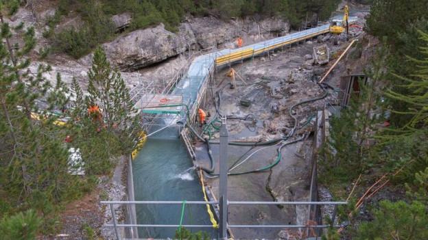 in Lightbox öffnen. Bildlegende: Mit grossem Aufwand wird der Spöl gesäubert. Teilweise muss das Flussbett ausgebaggert werden.