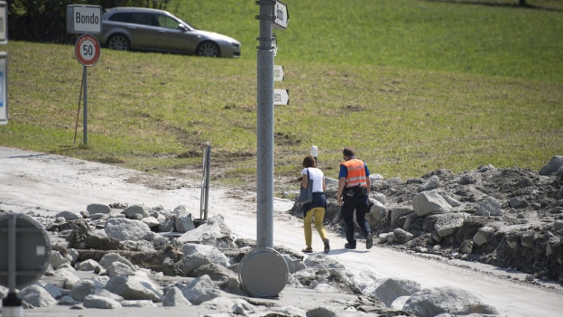 Ein Polizist begleitet eine Einwohnerin zurück ins Dorf Bondo.