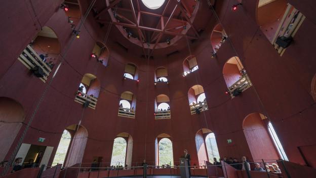 Dreistöckiger roter Holzbau mit Fenstern, Innenaufnahme mit Durchsicht auf Berghänge