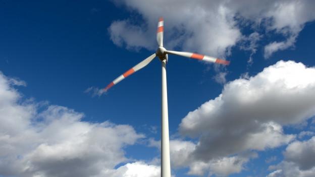Windrad mit drei Rotorblättern gegen blauen Himmel