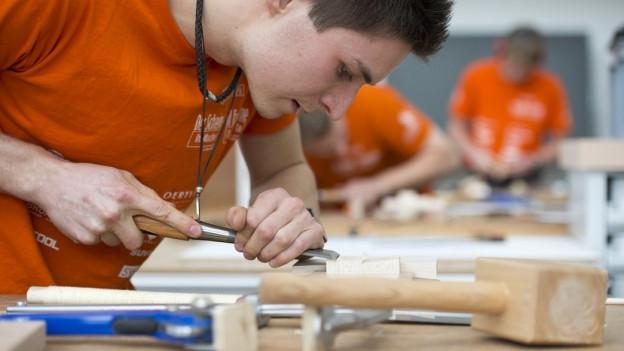 Schreiner Lehrling mit Spachtel bearbeitet Holzstück