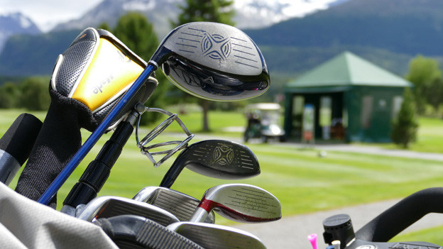 Golfschläger vor grünem Rasen.