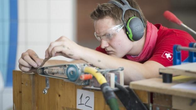 Mann arbeitet konzentriert am Schleifband