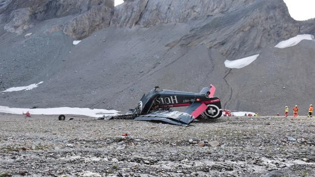 in felsigem Gelände liegt ein abgestürztes Flugzeug.