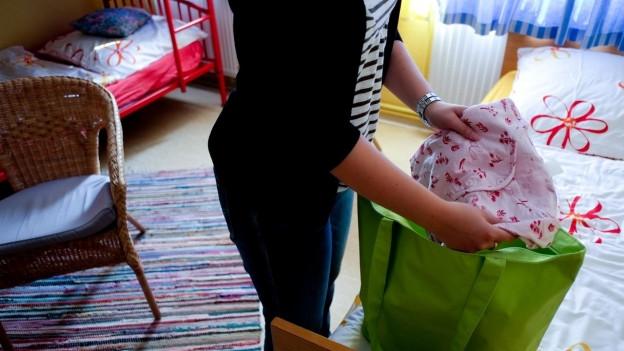Eine Frau packt Kleider in eine Tasche.