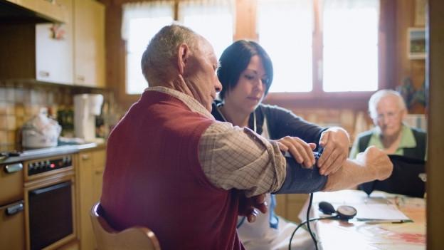 Eine Spitexmitarbeiterin misst einem Patienten den Blutdruck