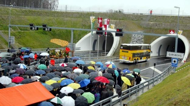 Menschenmenge mit Schirmen vor Tunneleinfahrt.