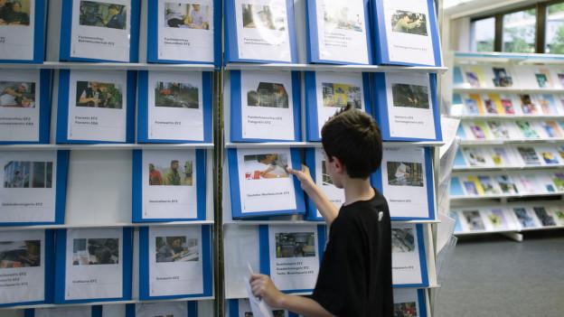 Junge nimmt Mappe mit Berufsinformationen aus einem Regal.