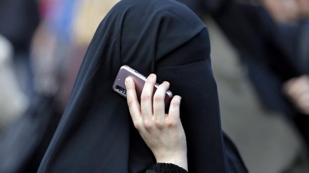 Burkaträgerin telefoniert mit Handy