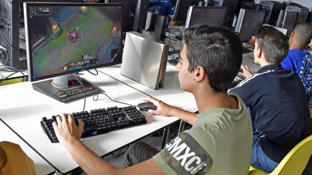 Jugendliche sitzen am Computer und machen ein Spiel