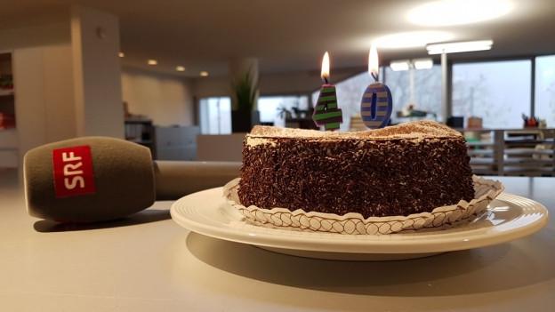 Torte mit Kerzen und ein Mikrophon daneben