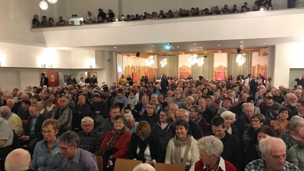 Viele Leute sitzen in einem Saal.
