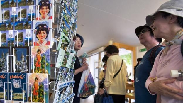 Touristin schaut postkarten an