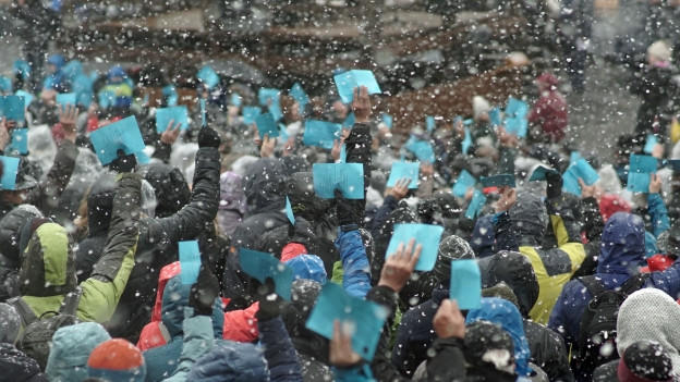 Hochgehobene Hände mit blauen Stimmzetteln im Schneeregen.