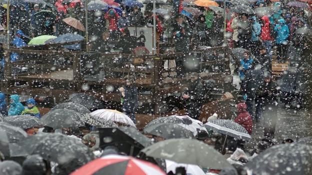 Die Besucher der Glarner Landsgemeinde schützen sich mit Schirm und Pellerine vor dem Schnee