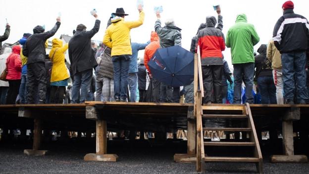 Menschen auf Holzkonstruktion von hinten