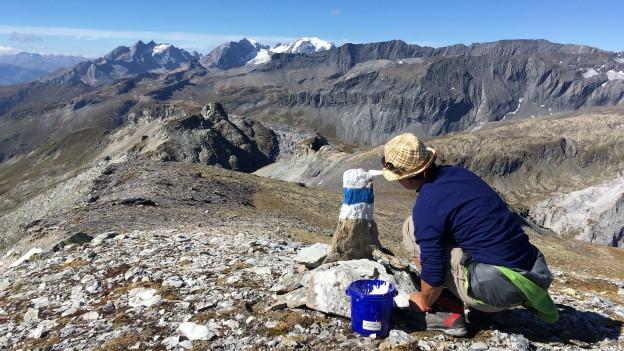 Frau malt einen Stein mit Blau-weisser Frarbe an