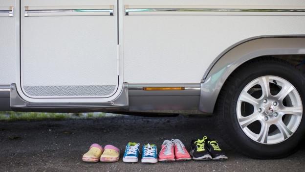 Schuhe stehen vor einem Wohnmobil