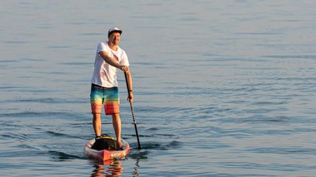 Mann mit Paddel steht auf Surfbrett im Wasser.