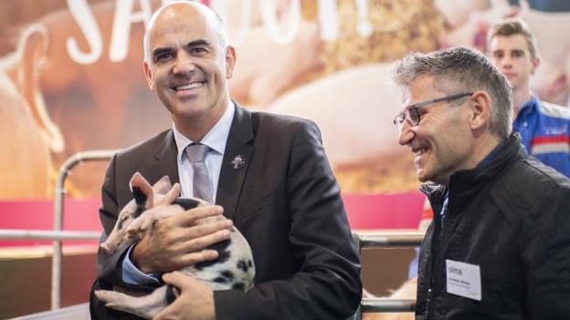 Bundesrat Alain Berset hält ein Säuli auf dem Arm
